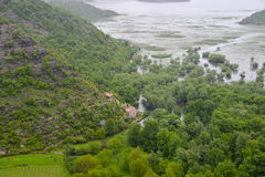 Small village. Surrounded by plants at the foot of the hill on the coast of Skadar Lake at Montenegro Royalty Free Stock Photo