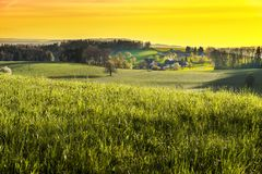 Small village in Alps. At sunset. Swiss landscape with forests and meadows early in the morning. Agriculture in Switzerland, arable land and pastures Stock Photo