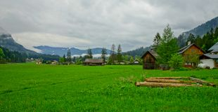 small village in Austria with grass meadow and small hill backgr royalty free stock photography
