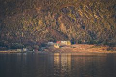 Small village at a base of a mountain. Small scandinavian fishing village at a base of a high mountain Stock Image