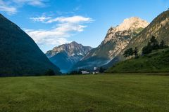 Village In Beautiful Green Mountain Valley At Sunrise. Small Village In Beautiful Fresh Green Mountain Valley At Sunrise Stock Image