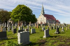 Small village cemetery and patrimonial neoclassical 1737 stone catholic church in Saint-Jean, Island of Orleans. Quebec, Canada stock image