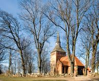 A small village church. A small church of Cisowo, Poland. Barren trees, a stone wall in front of it Stock Image