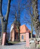 A small village church. A small church of Cisowo, Poland. Low perspective, a pavement leading to the church Stock Images