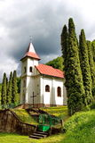 Small village church surrounded by trees with cloudscape on background Royalty Free Stock Image