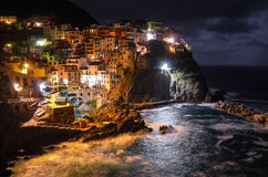 Small village on cliff, Manarola. Photo shows small village builded on cliff in Manarola in Cinque Terre (Italy). Colorfull houses, rough sea, waves crashing Stock Image