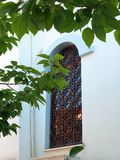 Small Village Greek Orthodox Church. Detail of a barred window on a small white Greek Orthodox church, with a leafy shade tree, in a small village on the Stock Images