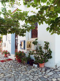 Small Village Greek Orthodox Church. Front exterior of a small white Greek Orthodox church, with flowers in pots and a leafy shade tree, in a small village on Stock Photos