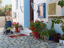 Small Village Greek Orthodox Church. Front exterior of a small white Greek Orthodox church, with flowers in pots and a leafy shade tree, in a small village on Royalty Free Stock Photography