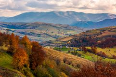 Small village on hills in autumn. Lovely countryside of Carpathian mountains. mighty ridge in the distance. red foliage on trees Stock Photos