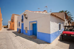 A small village on the island. Old houses. Caribbean style. The island of Tabarka in Spain. Summer heat. Sunny weather. Bright sun. Flower pots on the walls of Royalty Free Stock Photography