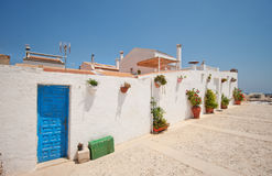 A small village on the island. Old houses. Caribbean style. The island of Tabarka in Spain. Summer heat. Sunny weather. Bright sun. Flower pots on the walls of Royalty Free Stock Photo