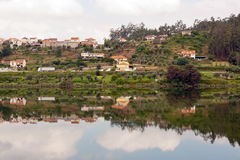 Small village with its reflection in the river. Landscape of a small village with its reflection in the river Stock Photography