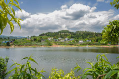 Small village on lakeside woody mountain in cloudy spring Royalty Free Stock Image