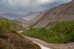 A small village lying in a rocky valley underlying blue cloudy sky with green pine trees and rice field. Gilgit, Pakistan royalty free stock image