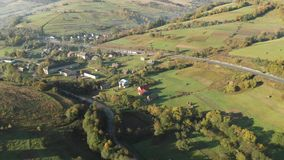 Small Village in the Mountains. Ukraine. Carpathian mountains. Aerial View Of The Landscape With Small Village In Mountains, Highway Through the Village in the stock video footage