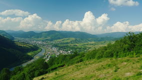 A small village near the river. Against the background of the mountains covered with forest. Ski resort in summer, rest. In the mountains. View from the ski stock video footage