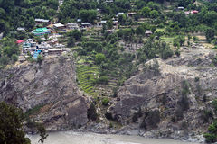 Small village reside close to falling rock formation along river at Himachal Pradesh. Cascade of houses along river bank Stock Photo