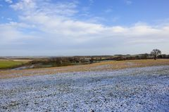 Snowy Winter landscape with a rural village and arable fields. A small village in the scenic yorkshire wolds with a light covering of snow with woodland and Stock Photography
