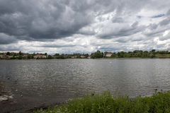 A small village on the shore of a large pond and dark, terrifying clouds above it. In Bohemia Stock Photo