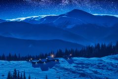 A small village on a snow covered mountain ridge. In a moonlight. The starry sky above the carpathian mountains Stock Image