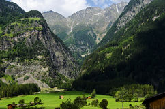 Small village surrounded with grass at the foot of Alps mountains Royalty Free Stock Photo