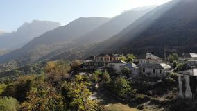 Small village under misty scenery mountains background. Aerial shot stock footage