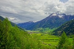 A small village in a valley with green field and cloudy sky. Austria royalty free stock images