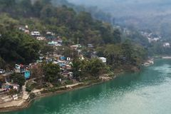 Small village located on picturesque slopes of the mountain at t. The small village which located on picturesque slopes of the mountain at the river bank with royalty free stock images