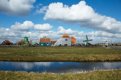 Small village with windmills and blue sky. Dutch traditional village with pond in foreground. Blue skies and fluffy clouds are reflected in the water. Image Stock Photography