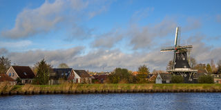 Small village of Woltersum. View of historic wooden windmill in the small village of Woltersum from the water in the Province of Groningen, Netherlands Royalty Free Stock Image