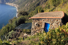 Small Vineyard House above the Sea. A small stone house with a blue door is located high above the sea Stock Images