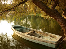 Small vintage boat in the sunset stock images