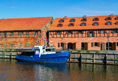 Small vintage fishing boat is docked at the quay. Of Dane river. Lithuania Stock Photography