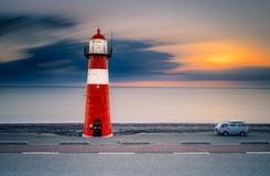 Traditional red and white colored lighthouse against twilight along the Dutch coastline at night
