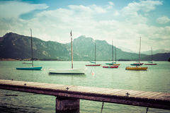 Small vintage sailboats anchoring. Alpine lake, landing stage and mountains. Royalty Free Stock Images