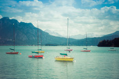 Small vintage sailboats anchoring. Alpine lake and mountains. Retro style. Royalty Free Stock Images