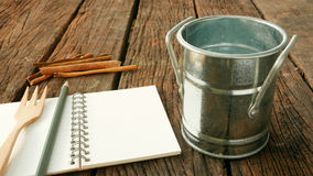 Small vintage zinc pot with blank earth tone note book on old dark brown wooden planks Royalty Free Stock Photos
