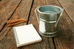 The small vintage zinc pot and cinnamon with blank earth tone note book Stock Images
