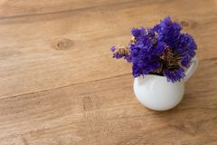 Small violet flower in a white cup on a wooden table royalty free stock photo