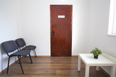 Small Waiting Room with Closed Door. Small white waiting room without people. A doctor, dentist or other medical practitioner provides this room for the use of Stock Photos