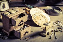 Small watchmaker`s room with spare parts of clocks. On wooden table stock photo