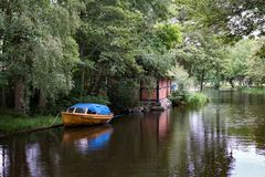 Small water canal for boat traffic in Sweden. Small water canal for boat traffic in Karlskrona, Sweden with an old wooden boat with blue canvas cover anchored at Stock Images