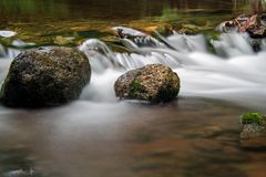 Small Water Drop Softened By Long Exposure On The Boyne River. A moss covered rock sits solid in the fast moving waters of the Boyne River, just upstream from royalty free stock photography