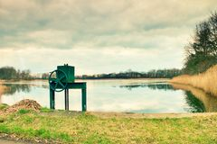 Small water reservoir, dam in autumn park. Locked control wheel at outlet. Stock Photos