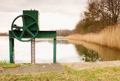 Small water reservoir, dam in autumn park. Locked control wheel at outlet. Stock Image