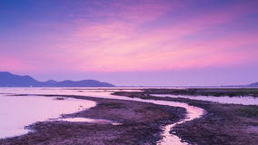 Small water way over lake and mountain background, dramatic sky after sunset Royalty Free Stock Images