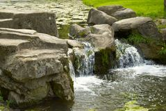 Small waterfall. Scenic view of small waterfall surrounded by boulders Stock Photo