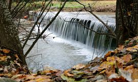 Small waterfall in autumn. Capture of a small beautiful waterfall behind fallen autumn leaves stock photo