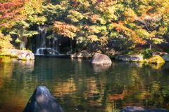 Small waterfall behind the bright colorful trees in autumn at Koko-en Garden in Japan. Bright autumn colors reflected in the pond at Koko-en Garden in Himeji stock photos
